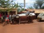 Bike panniers getting fixed beside a car getting fixed, tanzanian style.