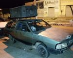 Ancient car with loudspeakers blaring from roof rack.